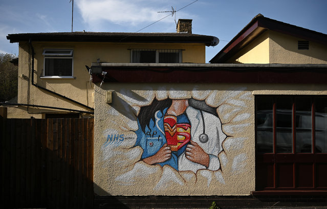 A picture shows graffiti depicting the badge of a superhero under a nurse's and doctor's uniform in homage to the efforts of NHS staff during the coronavirus crisis on a wall in Pontefract, northern England on April 14, 2020, as life in Britain continues during the nationwide lockdown to combat the novel coronavirus pandemic. The British government warned Monday it would not be lifting a nationwide lockdown anytime soon as the country remains in the grip of a coronavirus outbreak that has claimed more than 11,000 lives. (Photo by Oli Scarff/AFP Photo)