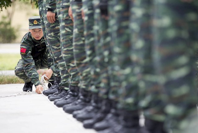 A soldier of China's People's Liberation Army uses a rope to line up other soldiers during a training session for a military parade to mark the 70th anniversary of the end of World War Two, at a military base in Beijing, China, September 1, 2015. (Photo by Reuters/Stringer)