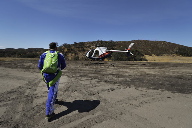 In this Monday, July 25, 2016 photo, skydiver Luke Aikins walks to a helicopter during his training in Simi Valley, Calif. (Photo by Jae C. Hong/AP Photo)