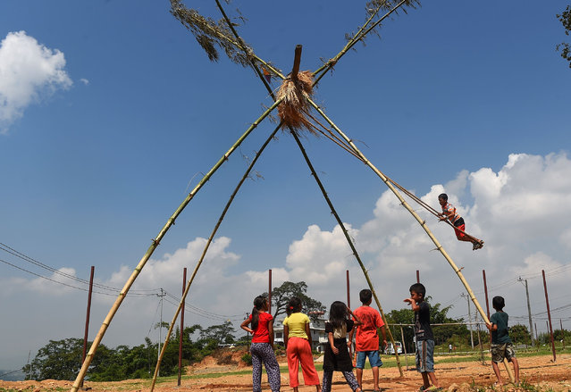 """A Nepali child plays on a swing, popularly known as the """"Dashain Ping"""", on the sixth day of the Hindu festival of Dashain in Lalitpur, on the outskirts of Kathmandu on September 26, 2017. People of all ages play on a swing in towns and villages, while marking the largest Hindu festival of Dashain in honour of the Hindu goddess of power, Durga. (Photo by Prakash Mathema/AFP Photo)"""