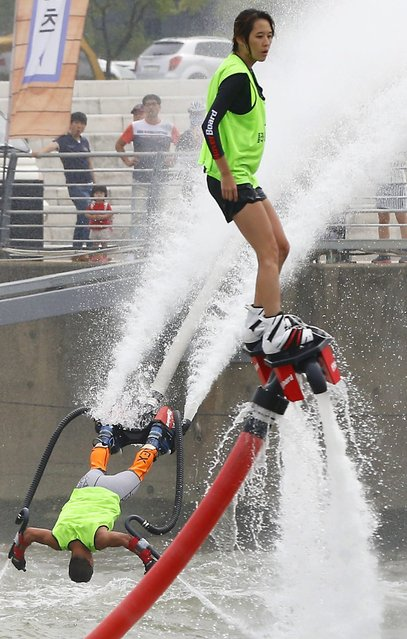 People use water jet pack machines during a flyboard competition on the Han River in Seoul South Korea, 24 August 2014. (Photo by EPA/Yonhap)