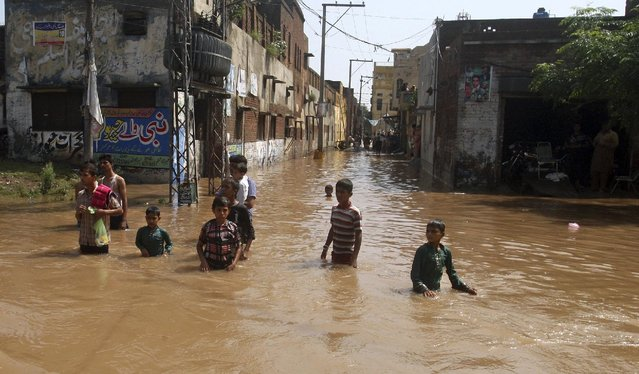 Youths wade through floodwater following heavy monsoon rains in Wazirabad, some 100 kilometers (65 miles) north of Lahore, Pakistan, Sunday, September 7, 2014. (Photo by K. M. Chaudary/AP Photo)