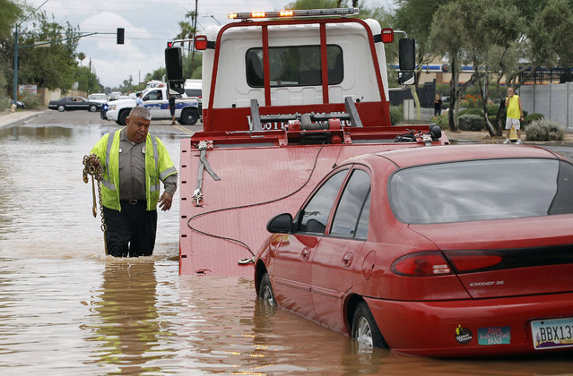 Steven Martinez of Western Towing prepares to lift a vehicle stranded in about two feet of water near Roosevelt and 44th Avenue on Monday, September 8, 2014 in Phoenix. Monday's record breaking rainfall flooded several Phoenix-area freeways and local streets forcing closures with some areas reporting up to five inches of rain. (Photo by Ralph Freso/AP Photo)