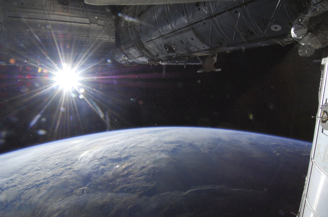 The sun is over Earth's horizon as seen from aboard the International Space Station above a point in southwestern Minnesota, May 21, 2013. (Photo by Reuters/NASA)