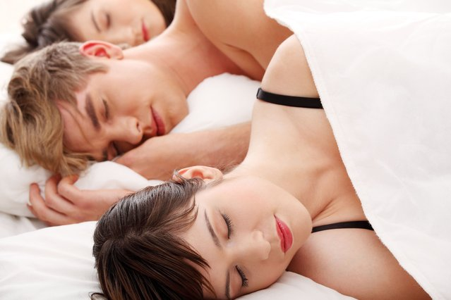 Threesome. Young man sleeping with two girls stock photo. (Photo by b-d-s/Getty Inages)
