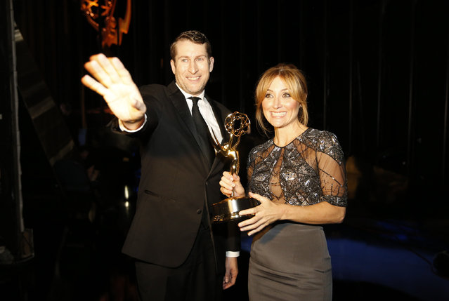Scott Aukerman, left, and Sasha Alexander pose backstage at the Television Academy's Creative Arts Emmy Awards at Microsoft Theater on Saturday, September 12, 2015, in Los Angeles. (Photo by Colin Young-Wolff/Invision for the Television Academy/AP Images)