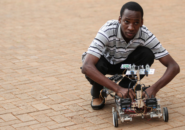 Alvin Kabwama, one of the designers of a prototype robot that can detect and disarm Improvised Explosive Devices attempts to switch it on at Makerere University's College of Engineering, Design Art and Telecommunication in Kampala, Uganda, on June 6, 2012. The robot is remotely controlled by a computer and can navigate a flat surface of up to a 20m radius. The development comes in the wake of continuous terrorist threats as a result of the country's contribution of forces to the African Union peace keeping mission in Somalia. (Photo by Edward Echwalu/Reuters)