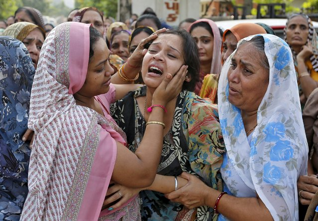 The daughter of Shantilal Boghra, who died in a cooking gas cylinder blast in central Madhya Pradesh state on Saturday, is consoled during the funeral of her father in Ahmedabad, India, September 13, 2015. (Photo by Amit Dave/Reuters)