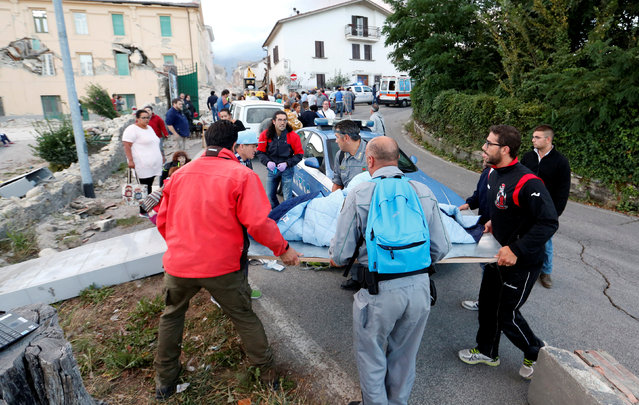 People stand along the road following a quake in Amatrice, central Italy, August 24, 2016. (Photo by Remo Casilli/Reuters)