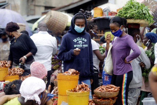 Women wearing face mask buy crayfish at a market in Lagos, Nigeria on Monday, May 4, 2020. Though Nigeria begun a phased easing of its strict lockdown measures on Monday, its confirmed cases of coronavirus continue to increase. (Photo by Sunday Alamba/AP Photo)