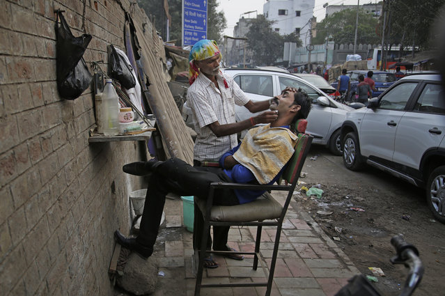 """In this November 15, 2017, photo, Dinesh, 55, who has been working for the last 20 years as a roadside barber attends to a customer in New Delhi, India. Dinesh, who uses only one name,  sets up a mirror and chair on the sidewalk and typically earns about 100 rupees ($1.50) a day cutting men's hair and shaving them. He said he often thinks about returning to his family farm in the northeastern state of Bihar.""""I'm a poor man who is doing my work"""", he said. """"I have to feed my kids"""". He said if he had any spare money he would think about buying a pollution mask. What he does earn, he said, he spends on basics like salt and chapatti, a type of Indian bread. """"I'm old now. I will go to my home and do some farming, plow my field"""", he said. """"What else can I do?"""". (Photo by Altaf Qadri/AP Photo)"""