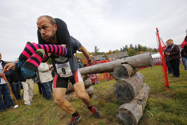 Eventual winners Jesse Wall carries Christina Arsenault over the first obstacle while competing in the North American Wife Carrying Championship at Sunday River ski resort in Newry, Maine October 11, 2014. REUTERS/Brian Snyder