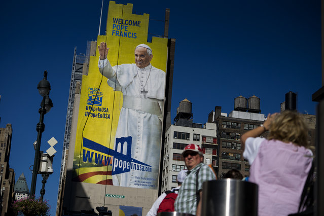 People wait on a taxi line near Madison Square Garden, Wednesday, September 23, 2015, as a 225-foot-tall hand-painted billboard of Pope Francis stands out at Eighth Avenue in New York. The billboard, designed by Israel Ochoa of DeSales Media, including a photo by photographer Giulio Napolitano, marks the arrival of the pope Thursday. (Photo by Craig Ruttle/AP Photo)