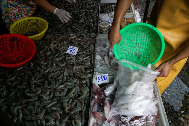 Vendors sort seafood at a market in Bangkok, Thailand, March 31, 2016. (Photo by Athit Perawongmetha/Reuters)