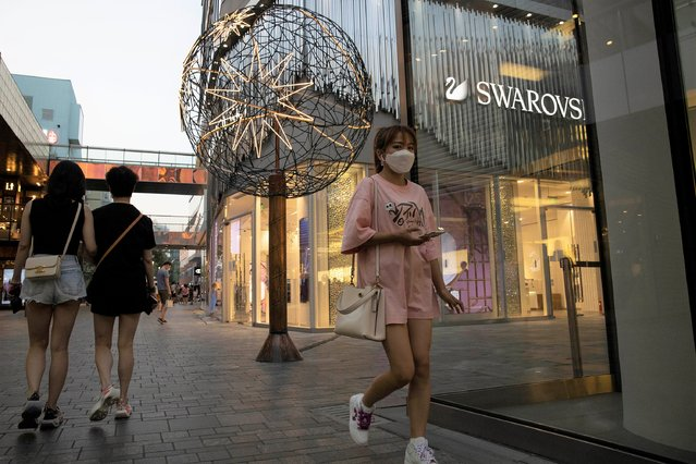 Shoppers pass through an affluent shopping district in Beijing on Tuesday, July 14, 2020. China's economy rebounded from a painful contraction to grow by 3.2% over a year earlier in the latest quarter as anti-virus lockdowns were lifted and factories and stores reopened. (Photo by Ng Han Guan/AP Photo)