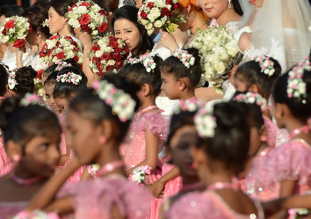 Chinese wedding couple and flower girls take part in a mass wedding ceremony of 50 Chinese couples in Colombo on December 17, 2017. (Photo by Ishara S. Kodikara/AFP Photo)