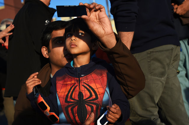Krishna Rao holds his son Prashant, 4, both of Ann Arbor, as they use a filter to see a partial solar eclipse along S. Ashley St. in Ann Arbor, Mich., on Thursday, October 23, 2014. Members of the University Lowbrow Astronomers set up several telescopes available for the public to use. (Photo by Melanie Maxwell/AP Photo/The Ann Arbor News)