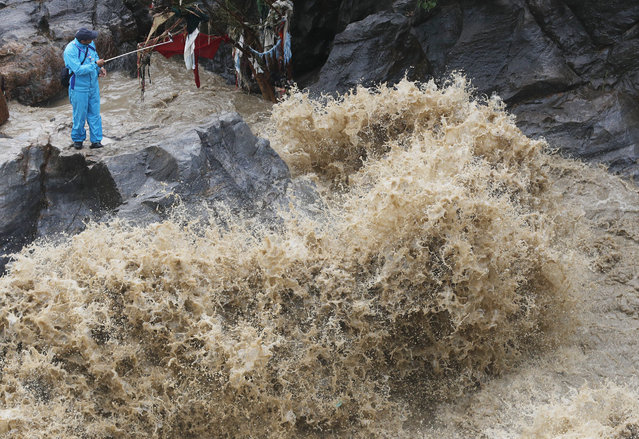 A Nepalese man takes selfie on the banks of flooded Bagmati river in Kathmandu, Nepal, Tuesday, July 21, 2020. Landslides and flooding caused by continuous heavy rainfall has blocked the main highway that connects Nepal's capital to most of the Himalayan nation blocking trucks bringing fuel and supplies, officials said Tuesday. (Photo by Niranjan Shrestha/AP Photo)