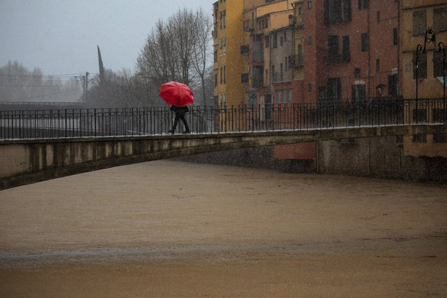 A woman holds an umbrella crossing a bridge over the river Onyar during a storm in Girona, Spain, on Thursday, January 23, 2020. Since Sunday the storm has hit mostly eastern areas of Spain with hail, heavy snow and high winds, while huge waves smashed into towns on the Mediterranean coast and nearby islands of Mallorca and Menorca. (Photo by Emilio Morenatti/AP Photo)