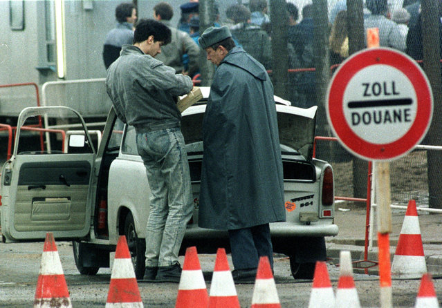 An East German civilian (L) shows an East German customs officer the contents of his Trabant (auto) at checkpoint Potsdamer Platz in East Berlin in this November 24, 1989 file picture, as East Germany enforcing stringent customs controls to avoid smuggling. (Photo by Reuters)