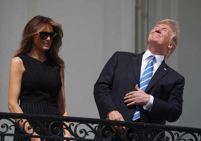 """President Donald Trump looks up toward the Solar Eclipse while joined by his wife first lady Melania Trump on the Truman Balcony at the White House on in Washington, DC on August 21, 2017. Millions of people have flocked to areas of the U.S. that are in the """"path of totality"""" in order to experience a total solar eclipse.  (Photo by Mark Wilson/Getty Images)"""