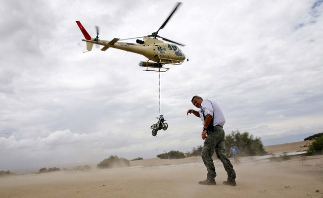 Dakar Rally Director Etienne Lavigne covers as sand is kicked up by a helicopter lifting the motorcycle of Herve Thierry of France after it fell in a river during the 11th stage of the 2013 Dakar Rally, January 16, 2013. (Photo by Bertrand Metayer/ Le Parisien)