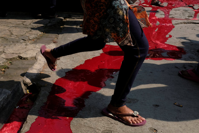 A girl jumps over the blood of a cow that was sacrificed for the Muslim holiday of Eid Al-Adha outside a mosque at Pasar Senin in Jakarta, Indonesia, September 12, 2016. (Photo by Reuters/Beawiharta)