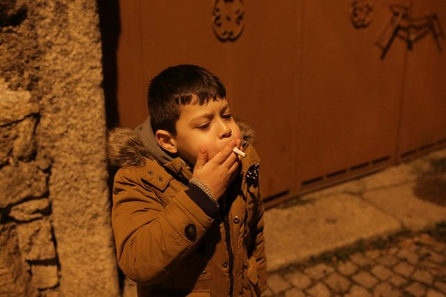 A young boy smokes in the street in the village of Vale de Salgueiro, northern Portugal, during the local Kings' Feast Friday, January 5, 2018. (Photo by Armando Franca/AP Photo)