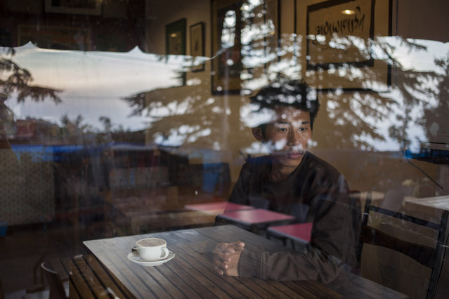 In this Tuesday, September 30, 2014 photo, Tashi Dorjee  27, sits in a coffee shop in Dharmsala, India. He fled with his brother as a four-year-old in 1991. Dorjee says he missed his parents most when he was in school, especially when everyone went home for winter vacation as he had no home to go to. He says because of time and distance there is no attachment with family and parents. (Photo by Tsering Topgyal/AP Photo)