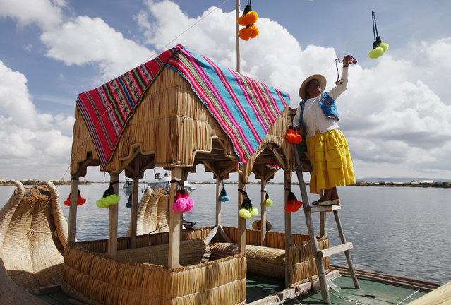 An Andean woman decorates a totora raft at the shores of a Uros island at Lake Titicaca before a re-enactment of the legend of Manco Capac and Mama Ocllo in Puno November 5, 2014. (Photo by Enrique Castro-Mendivil/Reuters)