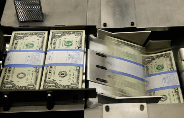 One dollar bills are put in packaging bands during production at the Bureau of Engraving and Printing in Washington November 14, 2014. (Photo by Gary Cameron/Reuters)