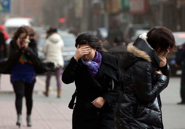 Chinese women brace through strong wind on a street as the capital city is hit by sandstorm in Beijing Thursday, February 28, 2013. (Photo by Andy Wong/AP Photo)