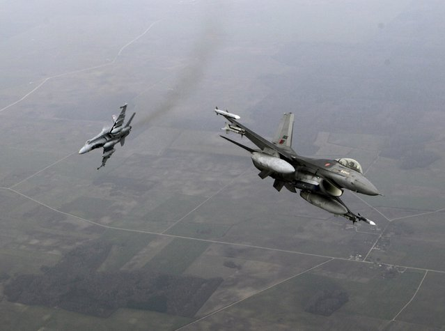 Portuguese Air Force fighter F-16 (R) and Canadian Air Force fighter CF-18 Hornet patrol over Baltics air space, from the Zokniai air base near Siauliai November 20, 2014. (Photo by Ints Kalnins/Reuters)