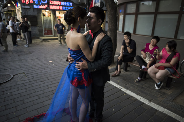 China has recently relaxed its one child policy that was used to control a burgeoning population. A couple has their wedding photo taken in an old quarter of Beijing on May 24, 2016. (Photo by Michael Robinson Chavez/The Washington Post)