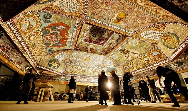 Visitors look at the the painted ceiling of a reconstructed wooden synagogue that dates back centuries during a presentation  to the media in Warsaw, Poland, on March 12, 2013. The painting in the17th century synagogue is a key attraction in the Museum of the History of Polish Jews, a major institution due to open next year in  Warsaw. (Photo by Czarek Sokolowski/Associated Press)
