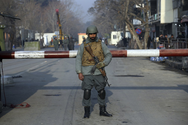 """A member of Afghan security forces stands guard following Saturday's suicide attack in Kabul, Afghanistan, Sunday, January 28, 2018. U.S. President Donald Trump is condemning """"the despicable car bombing attack"""" in the Afghan capital of Kabul. (Photo by Rahmat Gul/AP Photo)"""