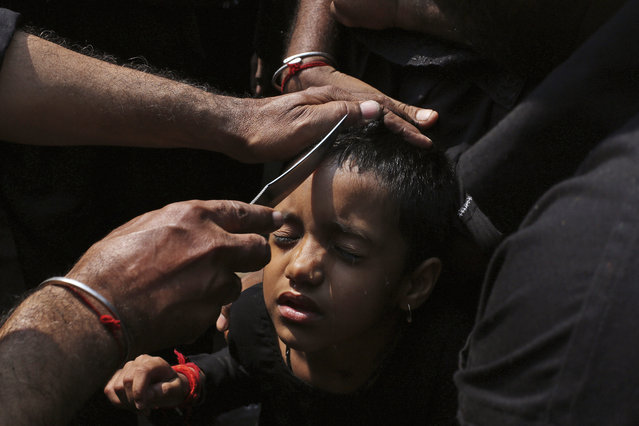 An Indian Shiite Muslim man prepares to make a cut on the forehead of a child with a knife during a procession to mark Ashoura in Hyderabad, India, Saturday, October 24, 2015. Ashoura is the 10th day of Muharram, the first month of the Islamic calendar, observed around the world in remembrance of the martyrdom of Imam Hussein, the grandson of Prophet Mohammed. (Photo by Mahesh Kumar A./AP Photo)