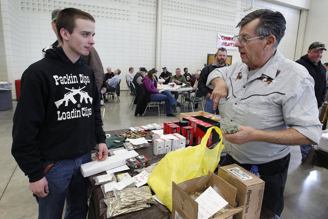 Roland Blanke, of Sheboygan Falls sells .223 gauge shells to Jeff Barelmann, of Cedarburg, that he says are becoming scarce because of Homeland Security, at the Washington County Fairgrounds Gun Show that drew thousands of people over the weekend, on March 22, 2013. (Photo by Gary Porter)