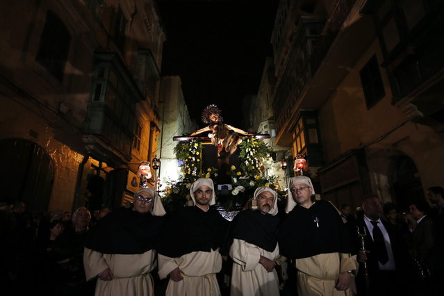 """The """"miraculous"""" Ta' Giezu (of Jesus) crucifix is carried during the Via Crucis, the Way of the Cross, during Holy Week in Valletta March 27, 2013. Legend has it that in 1630, the artist Fra Umile had racked his brains to try and depict Christ at his greatest hour of pain, but while he slept the head of Christ was completed by an angel. Holy Week is celebrated in many Christian traditions during the week before Easter. (Photo by Darrin Zammit Lupi/Reuters)"""