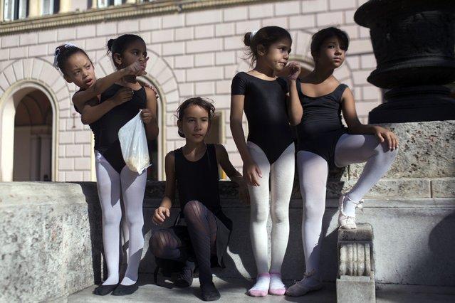 Girls wait to perform ballet at the Prado Boulevard in downtown Havana, December 5, 2014. (Photo by Alexandre Meneghini/Reuters)
