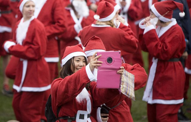 Runners dressed in Santa Claus take a selfie before they compete in the annual Santa Run in Victoria Park, east London December 7, 2014. (Photo by Neil Hall/Reuters)