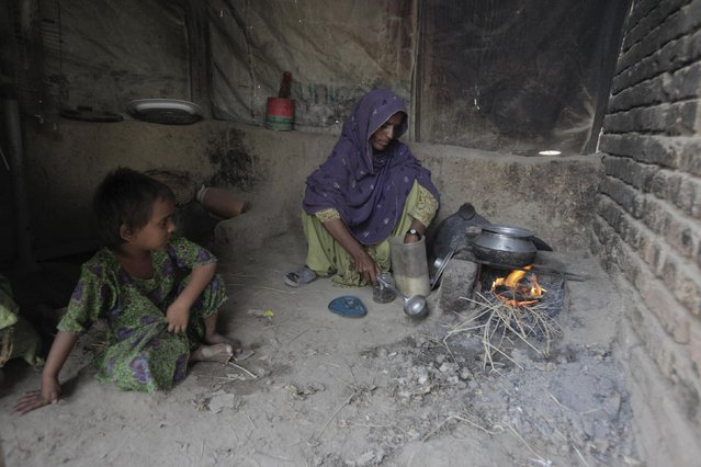 Sadori 35, a cotton picker, prepares a meal at her home in the evening after working in the cotton fields in Meeran Pur village, north of Karachi September 26, 2014. (Photo by Akhtar Soomro/Reuters)