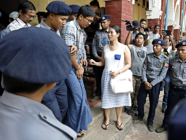 Detained Reuters journalist Wa Lone (C-L) talks with his wife Panei Mon (C) as he leaves the court in Yangon, Myanmar, 14 March 2018. Reuters journalists Wa Lone and Kyaw Soe Oo were arrested on the outskirts of Yangon on 12 December 2017 by Myanmar police for allegedly possessing classified police documents. (Photo by Nyein Chan Naing/EPA/EFE)