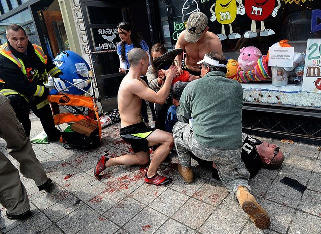 Bystanders tend to an injured man following explosions at the Boston Marathon in Boston, Massachusetts, April 15, 2013. (Photo by Ken McGagh/Reuters/MetroWest Daily News)