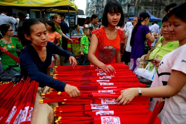 Myanmar Chinese women sell incenses sticks during a festival dedicated to Buddhist monk Shin Upagutta, celebrated by Myanmar's ethnic Chinese community, in Chinatown in Yangon October 21, 2015. (Photo by Soe Zeya Tun/Reuters)
