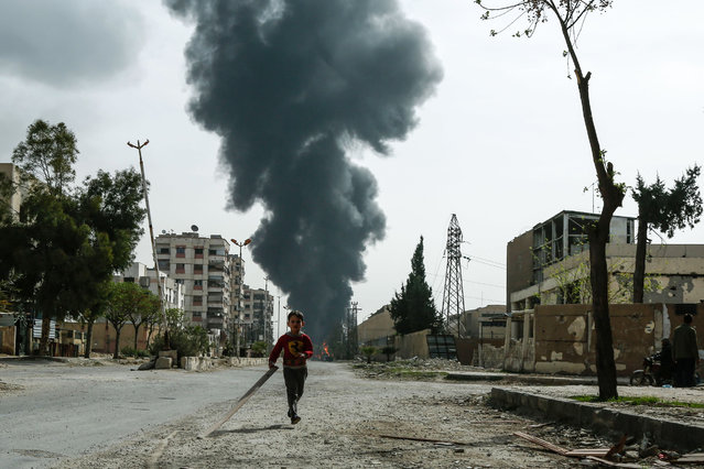 A child runs along a street in front of clouds of smoke billowing following a reported air strike on Douma, the main town of Syria's rebel enclave of Eastern Ghouta on March 20, 2018. (Photo by Muhammad Sadiq/AFP Photo)