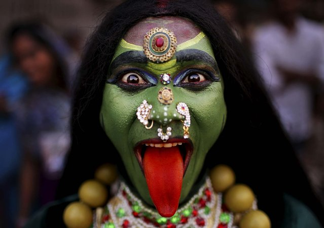 """A man dressed as the Hindu Goddess Kali participates in a religious procession as part of the """"Ram Navami"""" festival in New Delhi, India, on April 19, 2013. Ram Navami celebrates the birthday of Hindu god Rama. (Photo by Kevin Frayer/Associated Press)"""