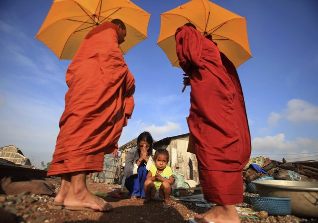 A woman and her daughter pray after offering alms to Buddhist monks near a railway track in Phnom Penh December 2, 2014. (Photo by Samrang Pring/Reuters)