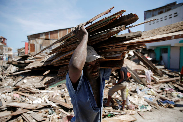 A man carries wooden planks after Hurricane Matthew passes in Jeremie, Haiti, October 8, 2016. (Photo by Carlos Garcia Rawlins/Reuters)