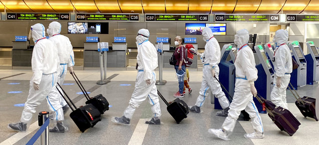 A woman, accompanied by a child, looks over as an airline crew wearing full personal protective equipment against COVID-19 walks through the international terminal at Los Angeles International Airport in Los Angeles on Tuesday, November 17, 2020. (Photo by Keith Birmingham/The Orange County Register via AP Photo)